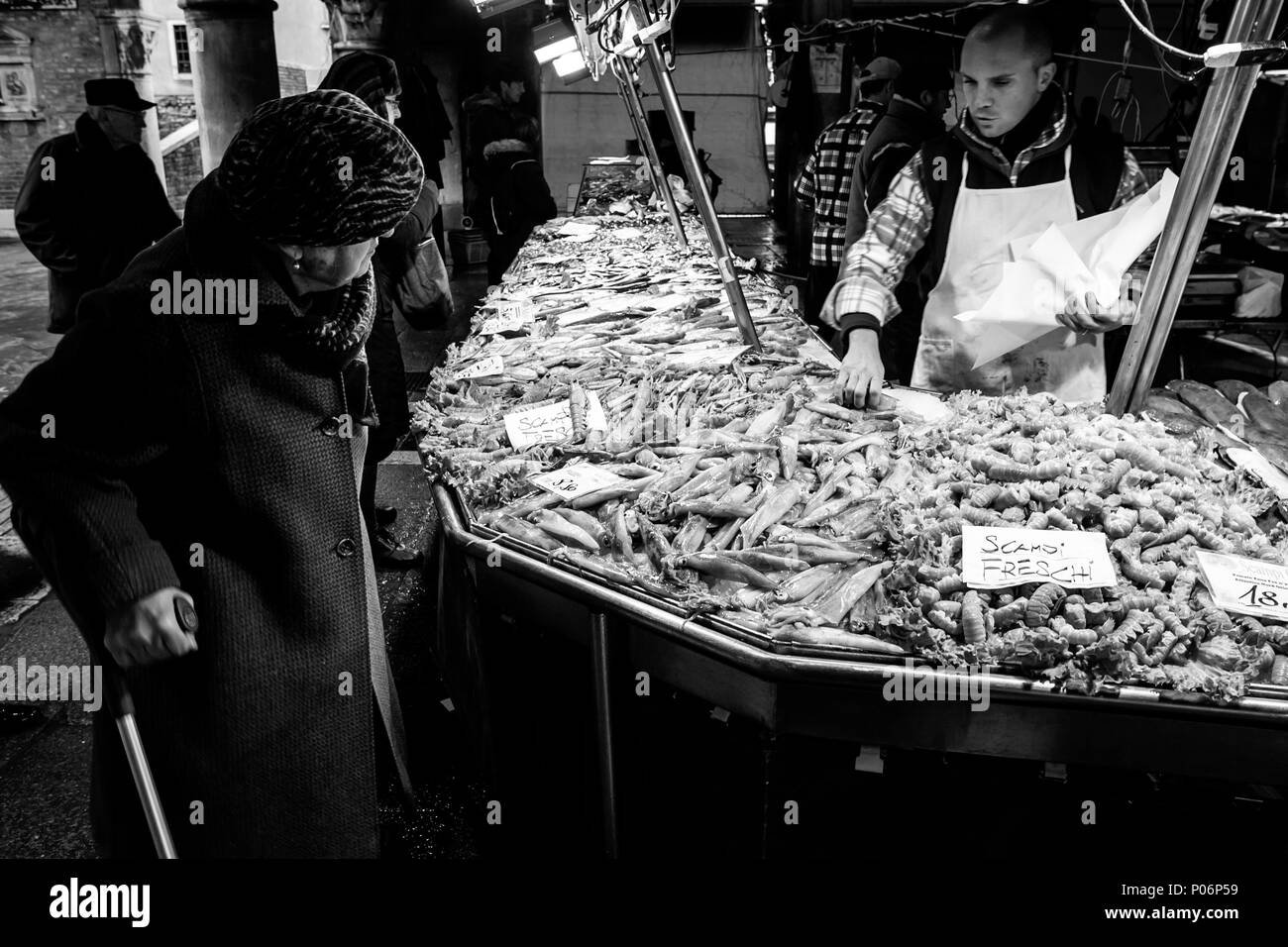 An Elderly Woman Buying Fresh Fish From The Market, Venice, Italy - Stock Image