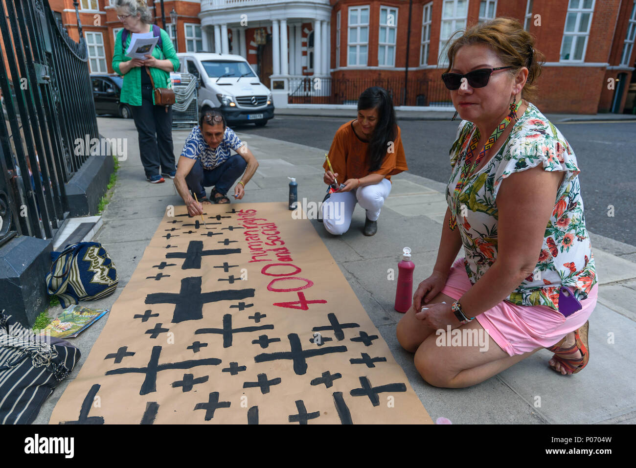 London, UK. 8th June 2018. People paint a banner about the 400 human rights and social activists murdered in Colombia at the  picket opposite the Colombian embassy supporting today's Gran Marcha Carnival in cities throughout Colombia demanding their government respects the rights of local communities against the interests of mining companies. Local residents voted against AngloGold Ashranti's huge La Colosa gold mine because of the extensive environmental damage it would cause. Credit: Peter Marshall/Alamy Live News - Stock Image