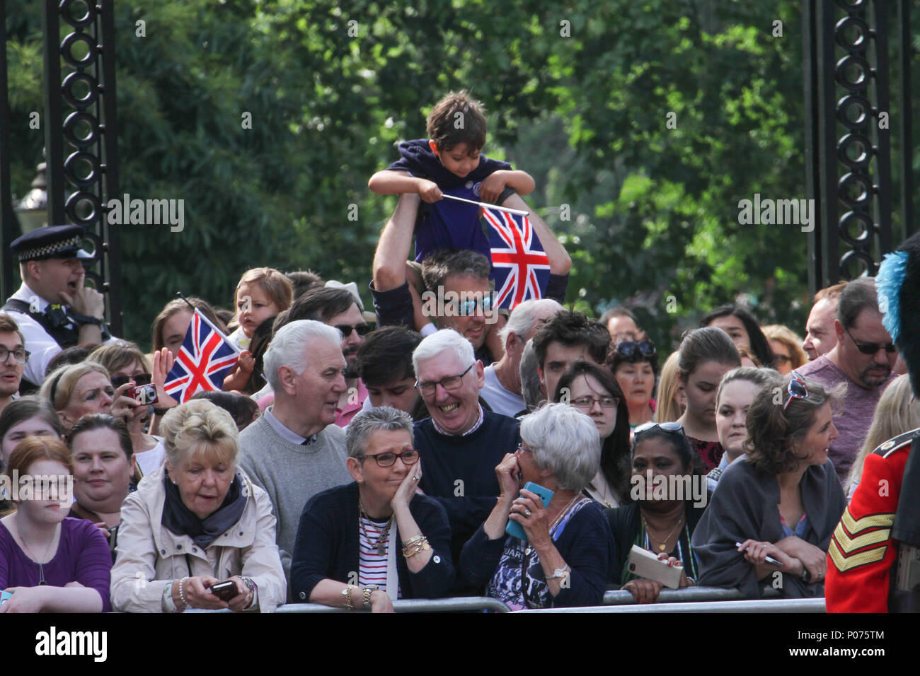 London, UK 9 June 2018: Members of the public seen along the Mall awaiting the  Royal Family on the way to the Horse Guards Parade Ground on 9 June 2018. Over 1400 parading soldiers, 200 horses and 400 musicians come together each June in a great display of military precision, horsemanship and fanfare to mark The Queen's official birthday. Credit: David Mbiyu/Alamy - Stock Image