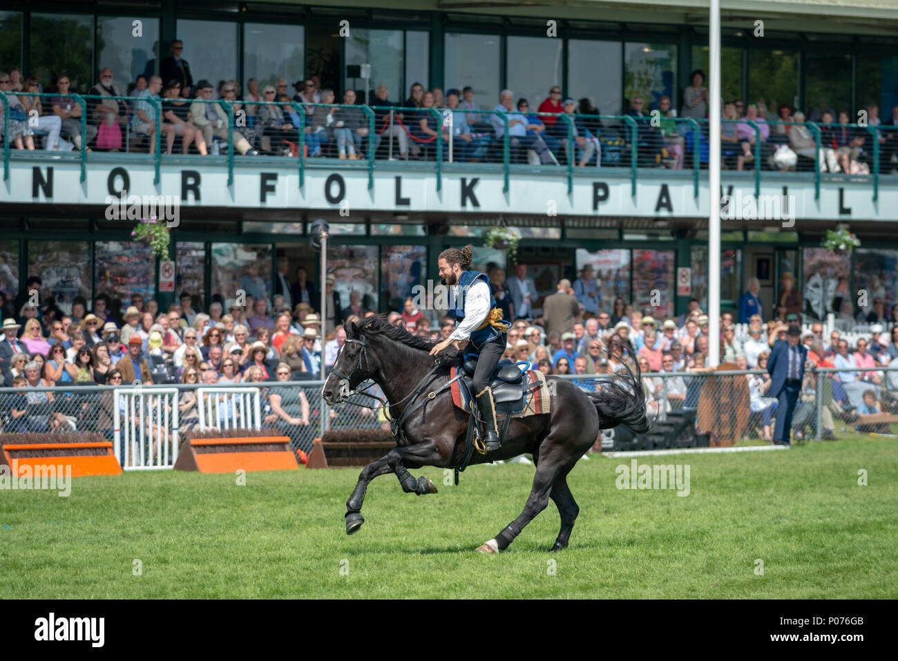While riding a horse, a rider from the Atkinson Action Horses gallops across the showground in front of thrilled spectators during a performance at the South Of England Show in Ardingly, Sussex, UK. Stock Photo