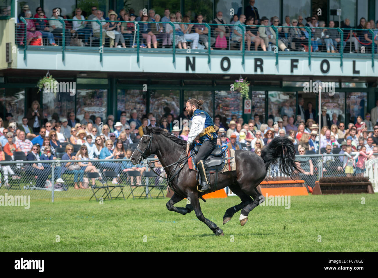 While riding a horse, a rider from the Atkinson Action Horses gallops across the showground in front of thrilled spectators during a performance at the South Of England Show in Ardingly, Sussex, UK. - Stock Image