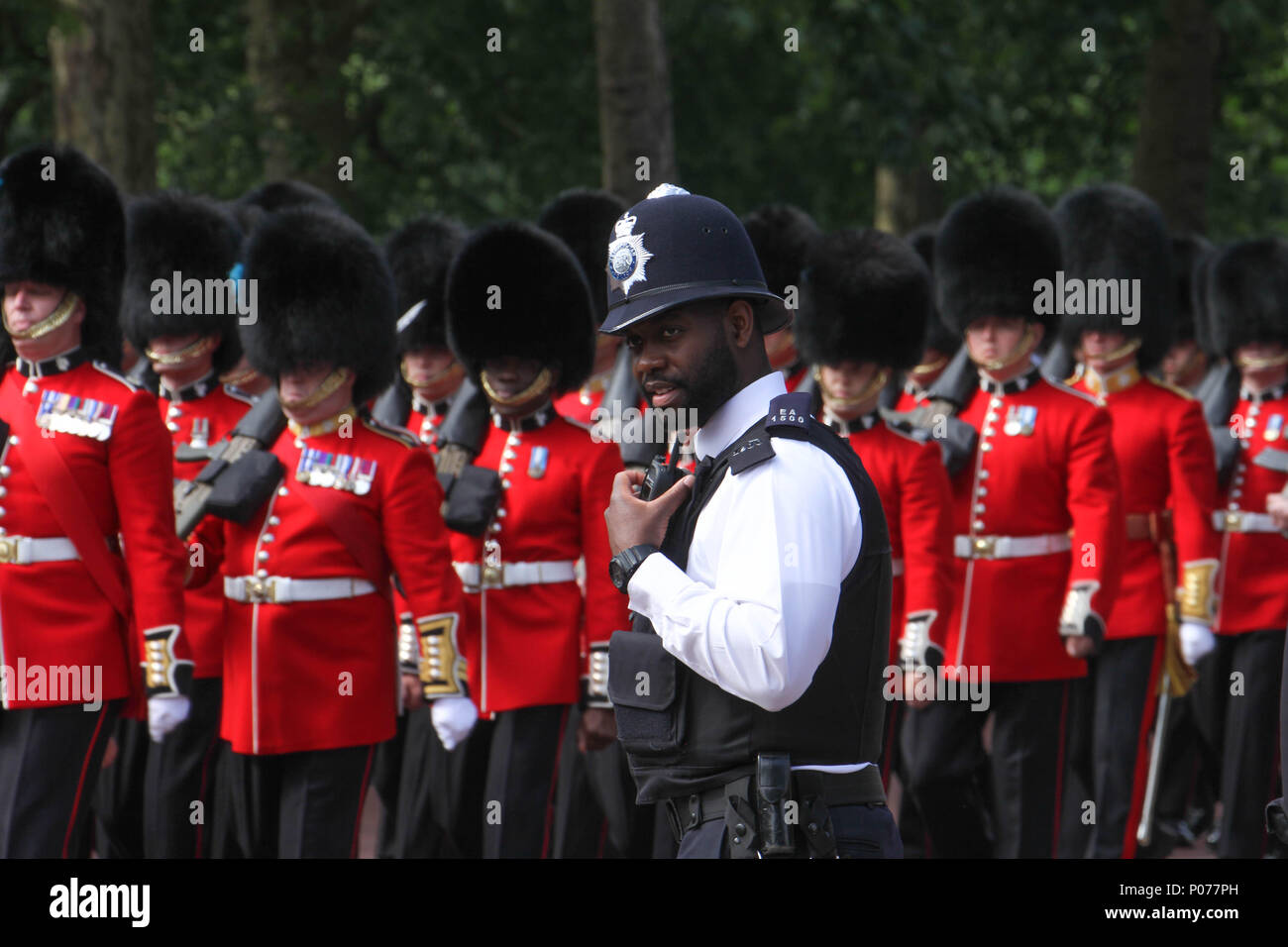 London, UK 9 June 2018: A black Metropolitan Police Officer seen by Hundreds of Guardsmen marching along the Mall to the Horse Guards Parade Ground as they make their way to the Horse Guards Parade Ground on 9 June 2018. Over 1400 parading soldiers, 200 horses and 400 musicians come together each June in a great display of military precision, horsemanship and fanfare to mark The Queen's official birthday. Credit: David Mbiyu - Stock Image