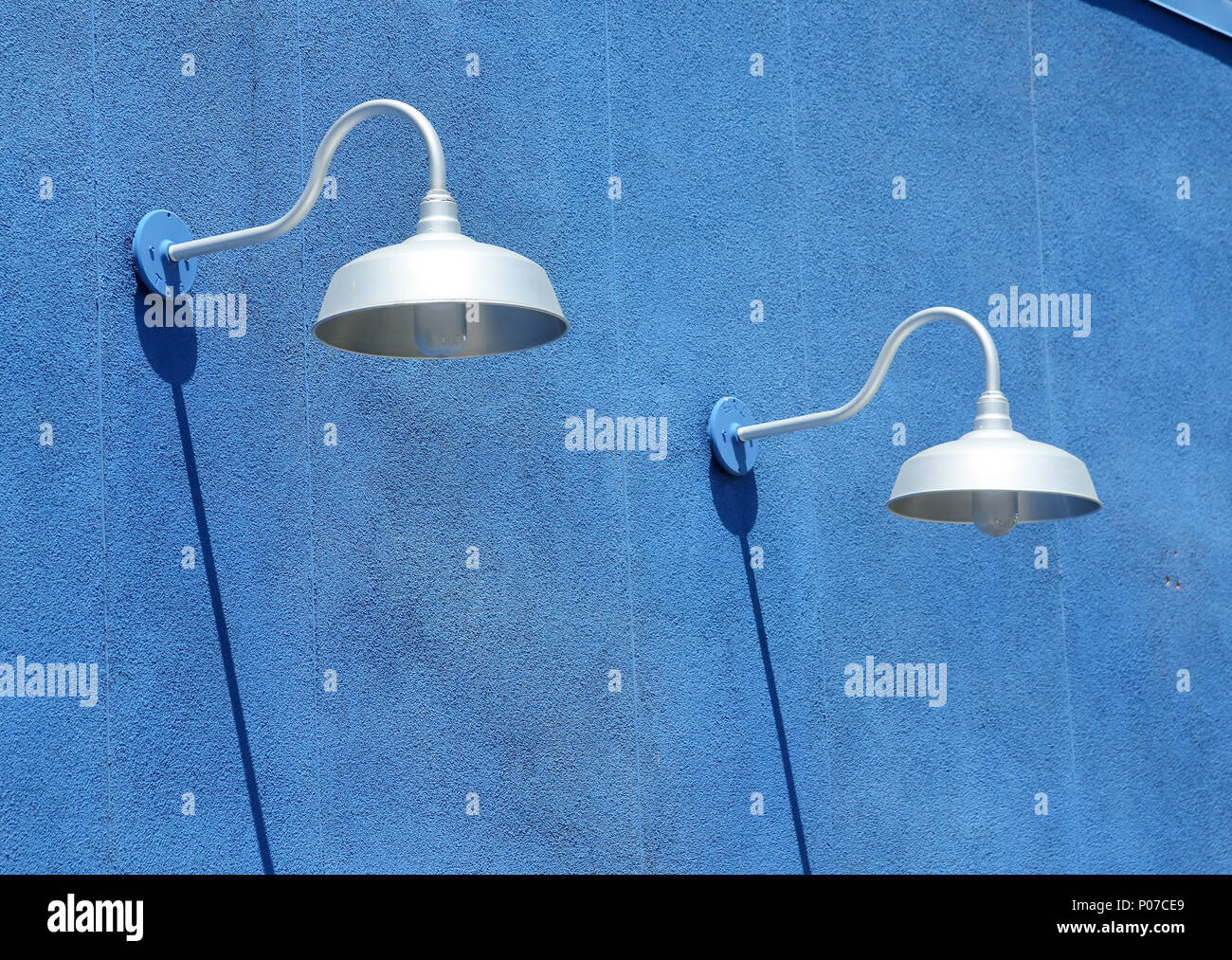 Blue stucco wall with light fixtures and shadows in daytime stock image