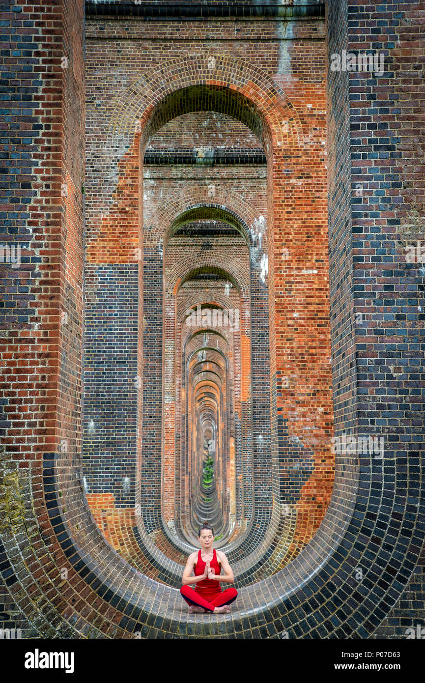 woman sitting in the arches of the Ouse Valley Viaduct practicing yoga and meditating Stock Photo