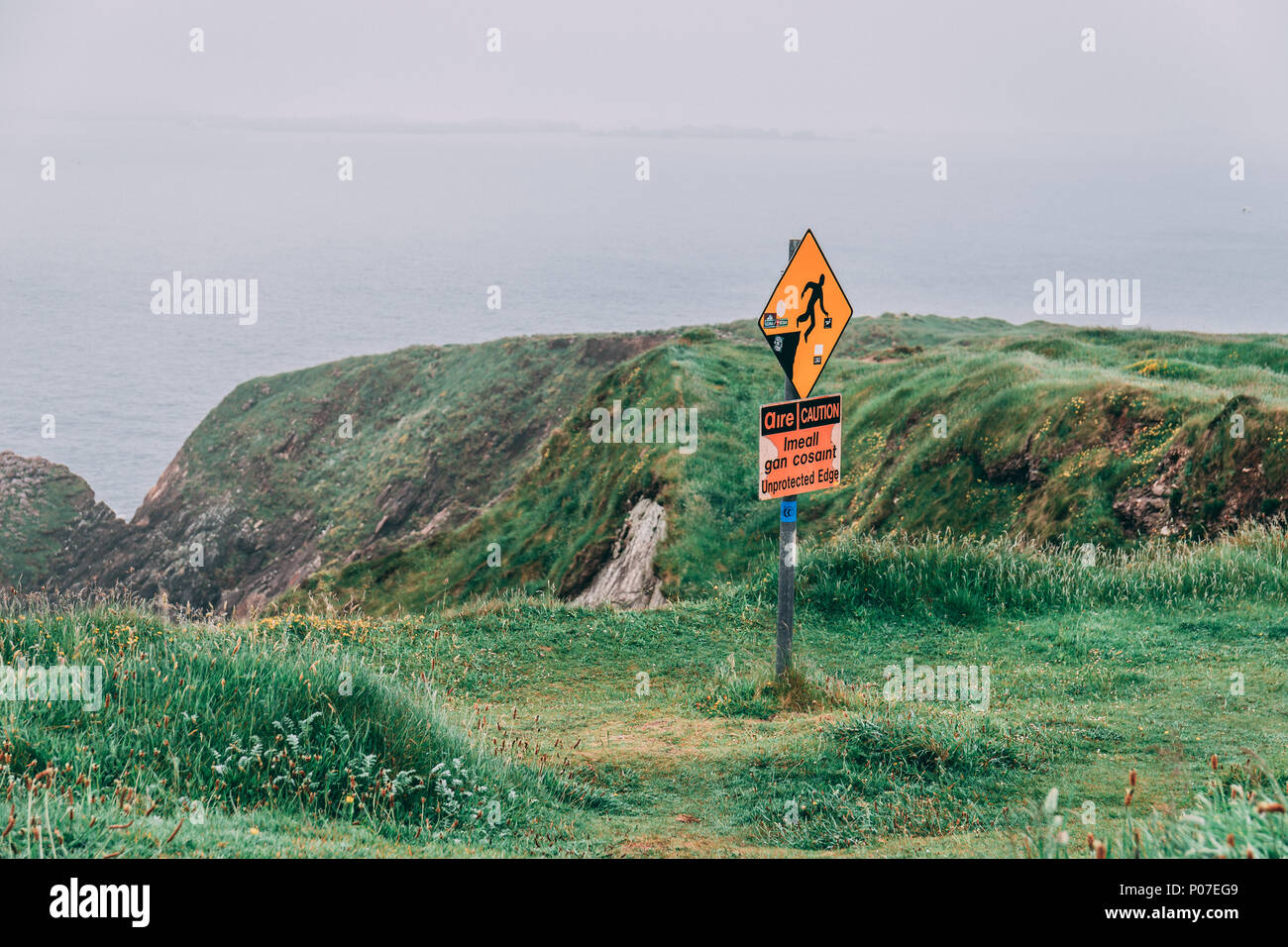 June 5th, 2018, Dunquin, Ireland - warning signs of slippery surface and unprotected edges at the iconic Dunquin harbour pier surroundings Stock Photo