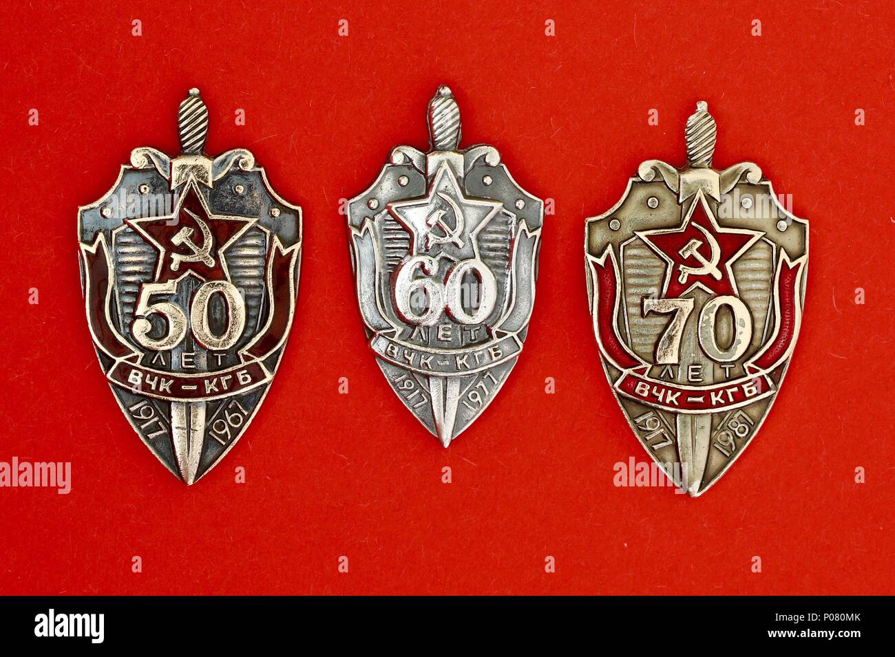 Three Russian KGB  badges commemorating 50, 60 and 70 years anniversaries. - Stock Image
