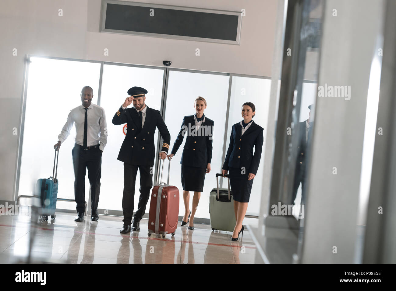 aviation personnel team walking by airport loggy with suitcases - Stock Image