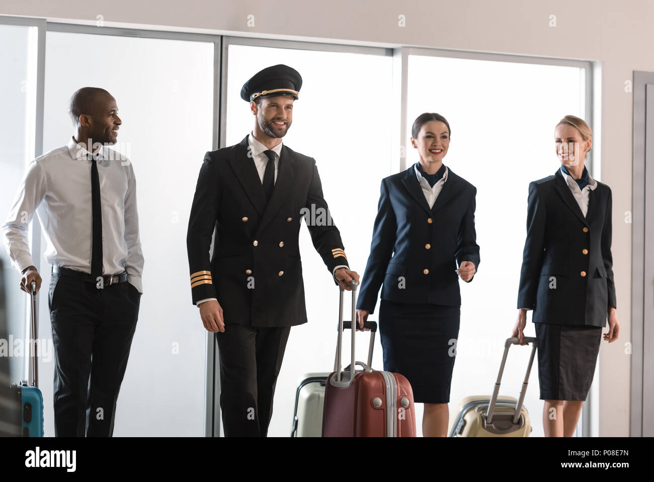 happy aviation personnel team walking by airport loggy with suitcases - Stock Image