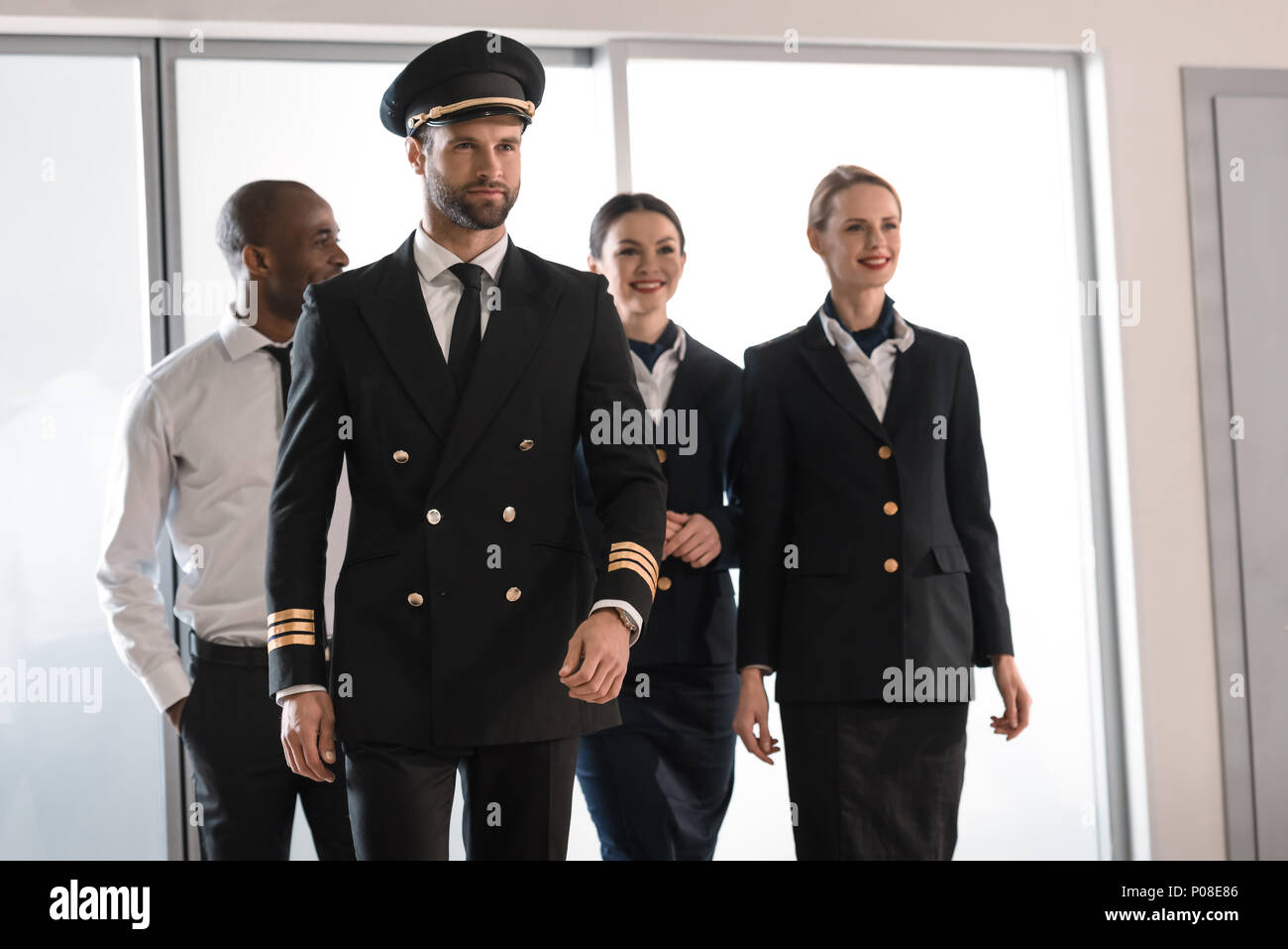 handsome pilot walking by airport with his team - Stock Image