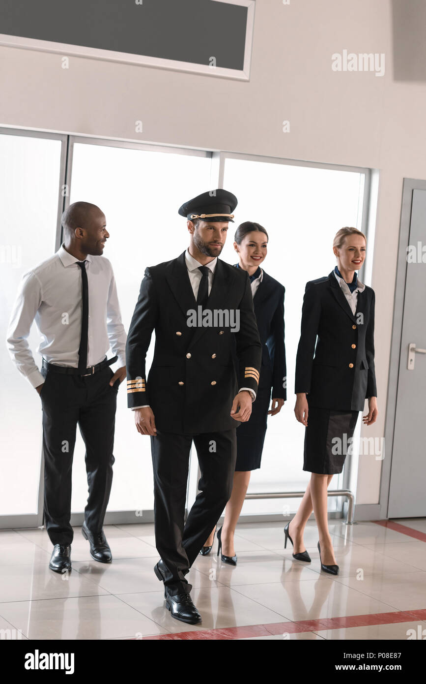 happy aviation personnel team in professional uniform walking by airport - Stock Image