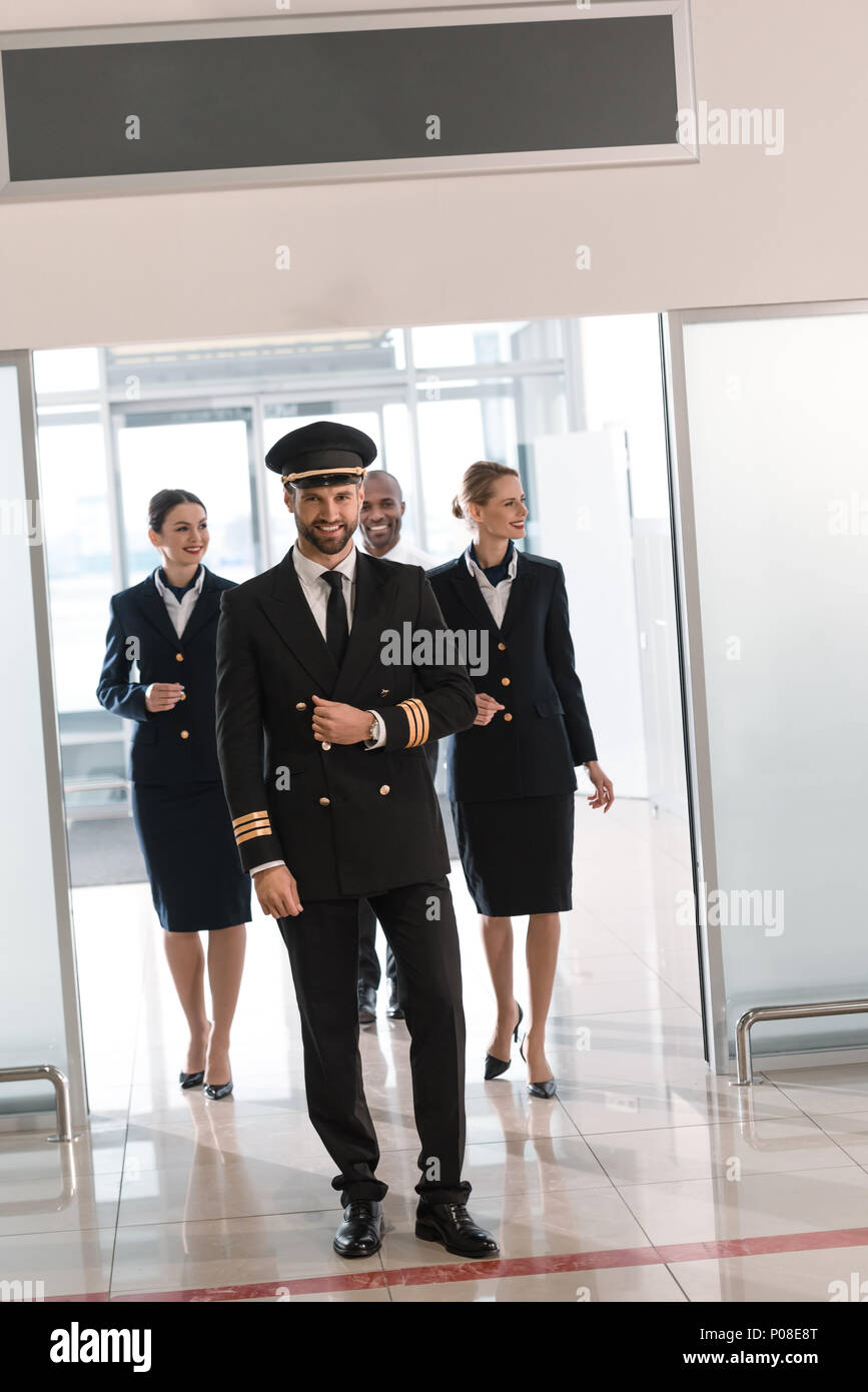 handsome young pilot walking by airport with his team - Stock Image