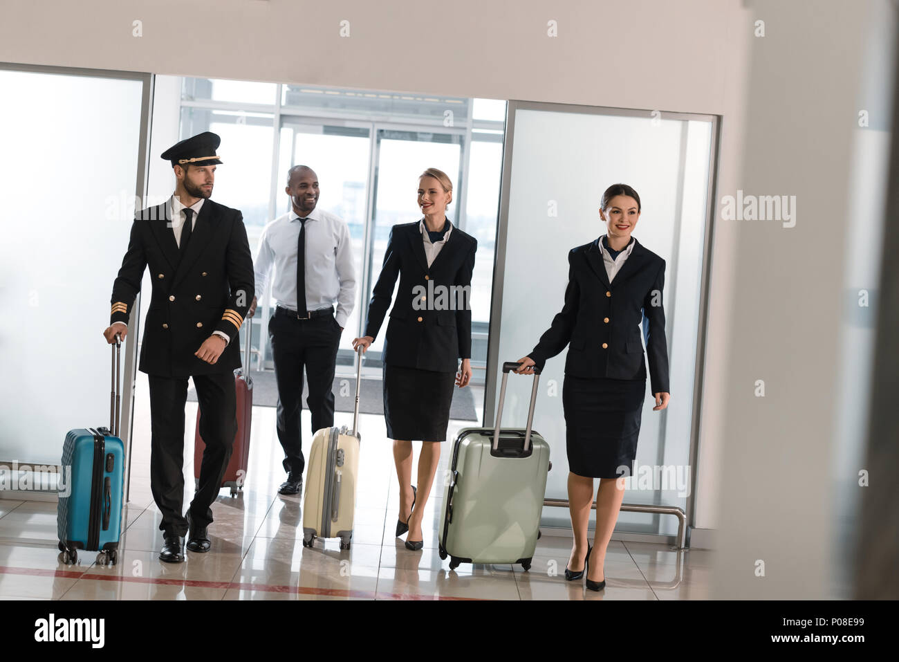 young aviation personnel team with suitcases at airport - Stock Image