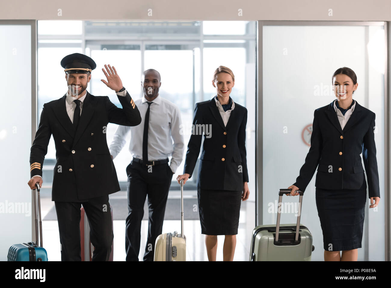 young aviation personnel team with suitcases at airport after flight - Stock Image