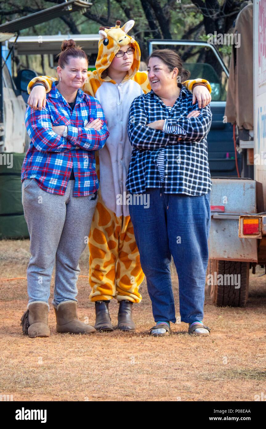 Gibb Challenge 2018 three women, one wearing a giraffe onesie, standing together at the morning meeting, Kimberley WA Australia. - Stock Image