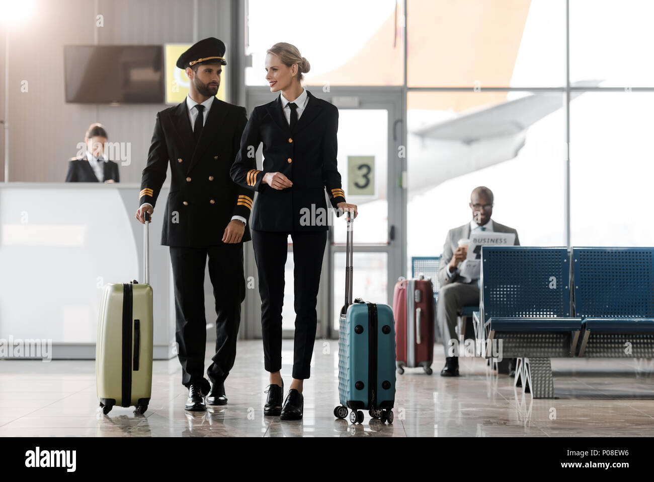 male and female pilots walking by airport lobby with suitcases - Stock Image