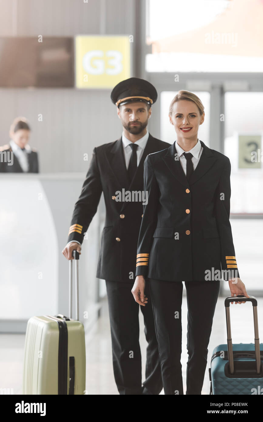 happy male and female pilots walking by airport lobby with suitcases - Stock Image