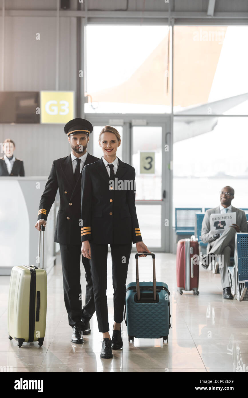 young male and female pilots walking by airport lobby with suitcases - Stock Image
