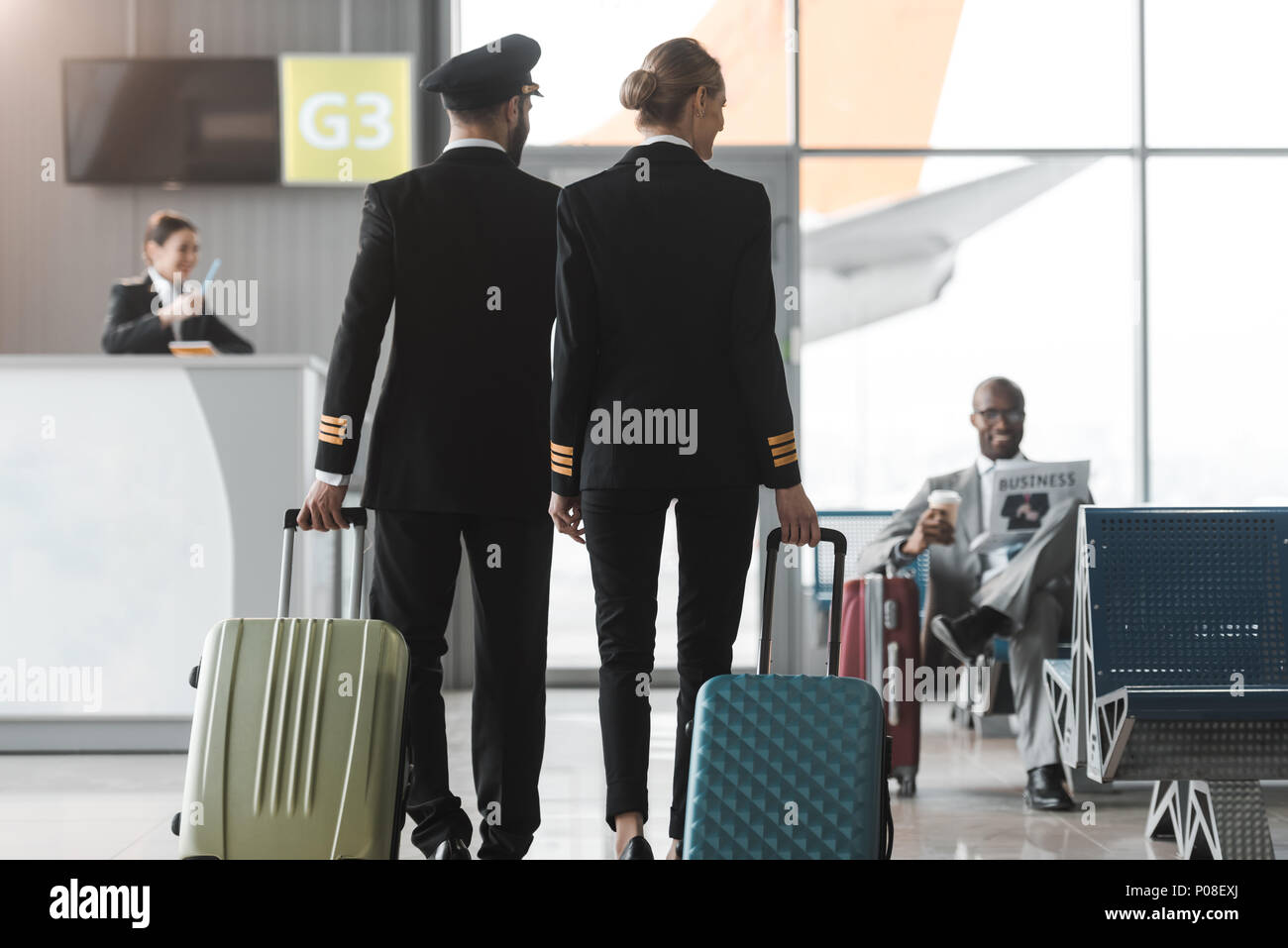 back view of male and female pilots walking by airport lobby with suitcases - Stock Image
