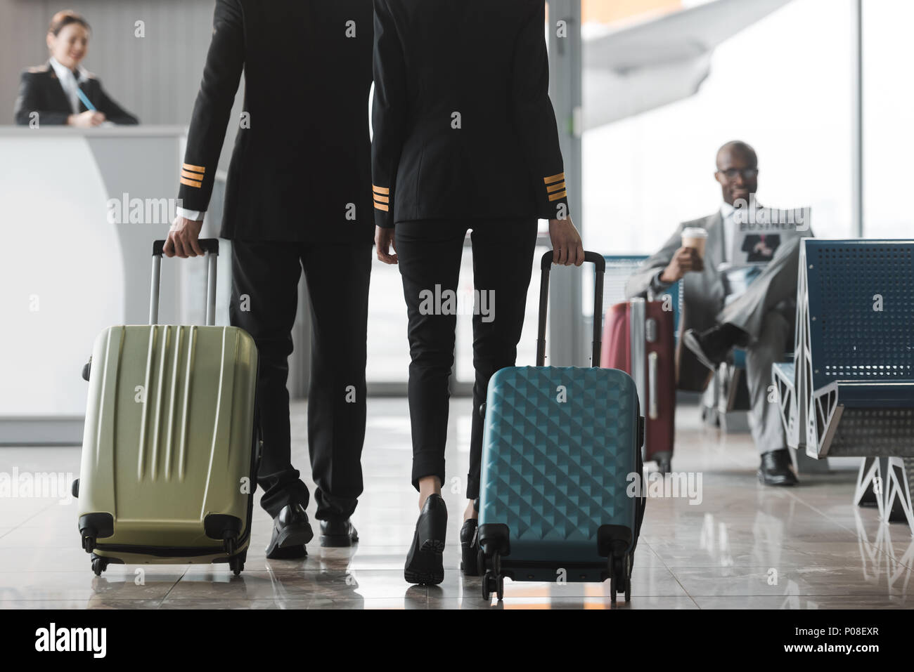 cropped shot of male and female pilots walking by airport lobby with suitcases - Stock Image