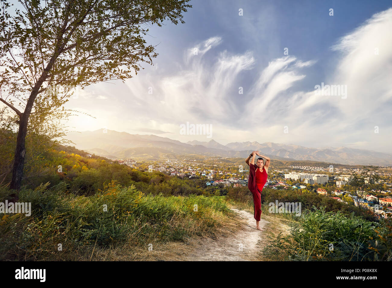 Fit man in red costume doing yoga leg split asana in the park with city and mountain on background in Kazakhstan - Stock Image