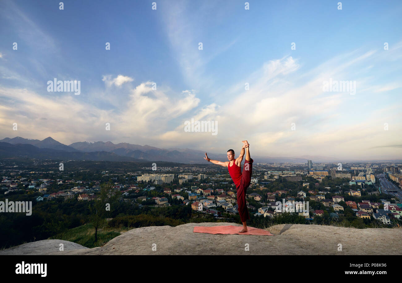 Fit man in red costume doing yoga balance asana in the park with city and mountain on background in Almaty, Kazakhstan - Stock Image