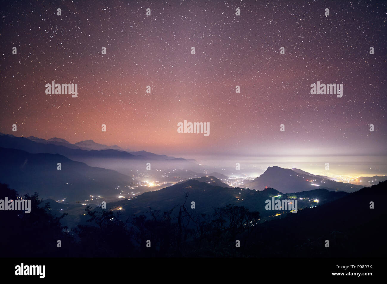 Lights of Pokhara city and villages at night starry sky at mountain range of Annapurna, Nepal - Stock Image