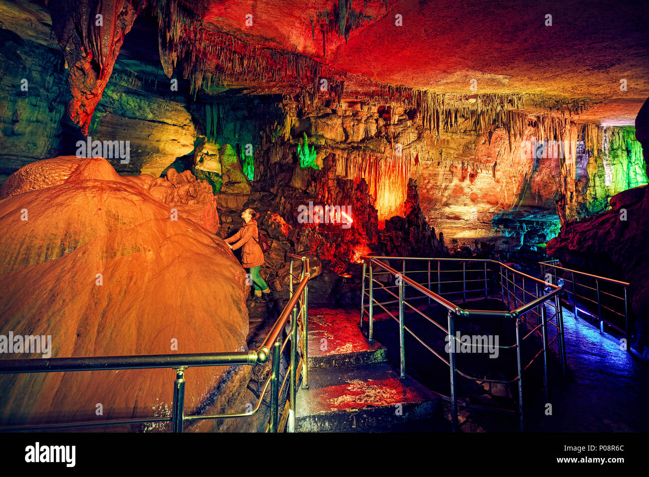 Tourist woman in underground cave Sataplia with colorful illumination in Kutaisi, Georgia - Stock Image