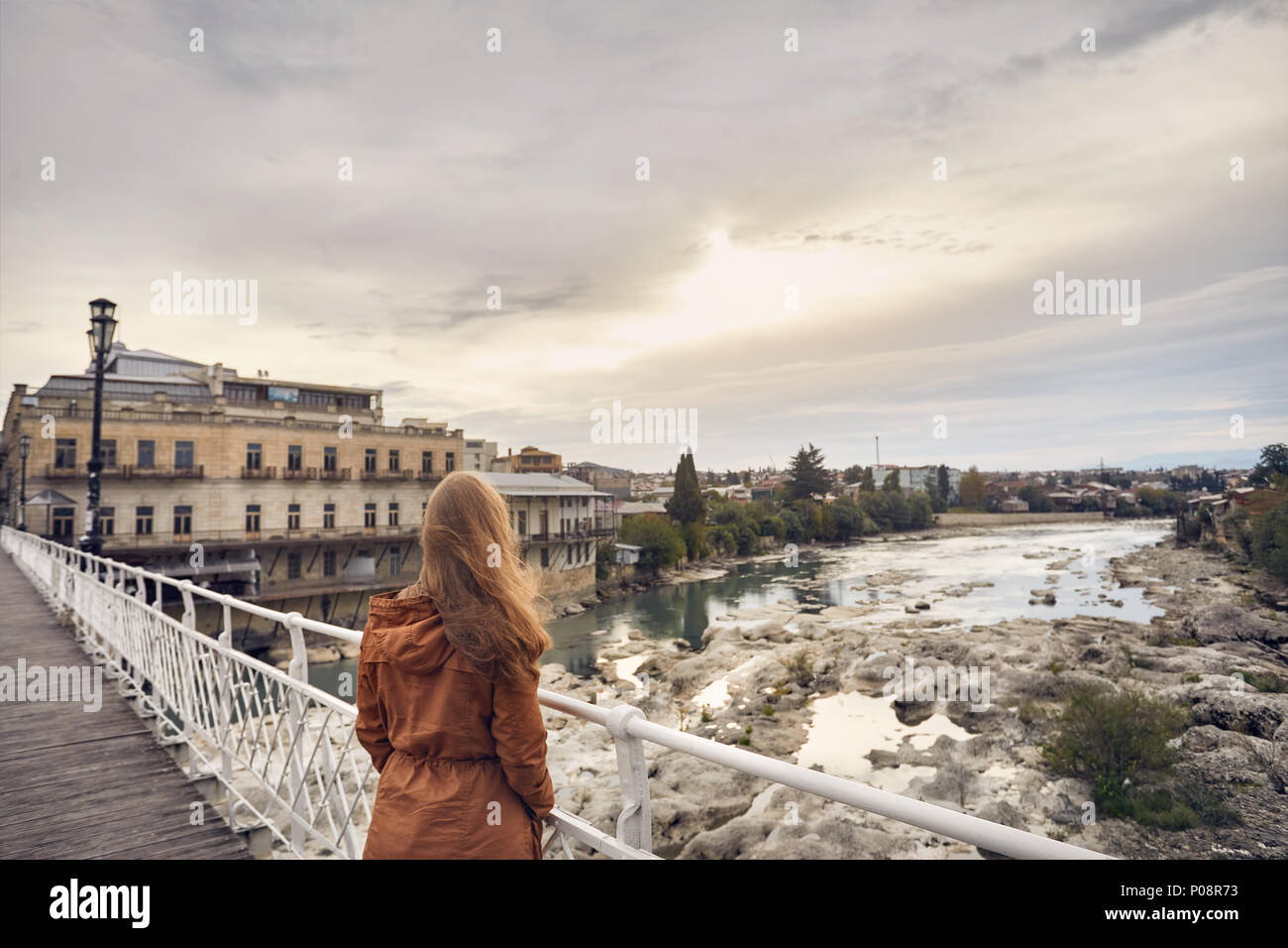Lonely woman with long hair on the bridge looking at sunrise in Kutaisi, Georgia Stock Photo