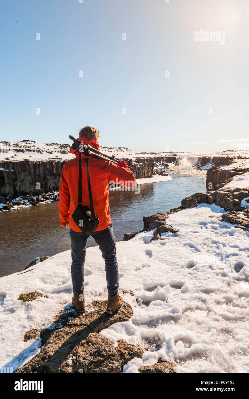 Man with camera equipment looking at Selfoss waterfall in winter, canyon, northern Iceland, Iceland - Stock Image
