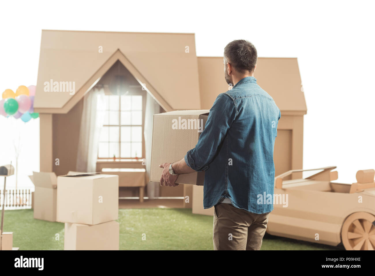 man with boxes moving into new cardboard house isolated on