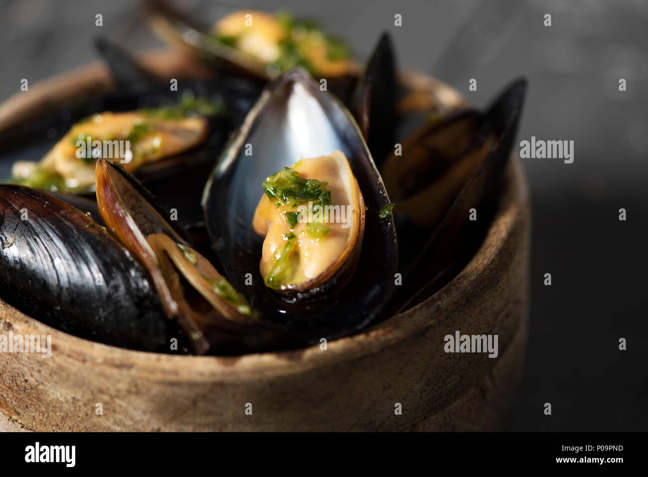closeup of a boxwood bowl with moules mariniere, a french recipe of mussels, on a rustic wooden table - Stock Image