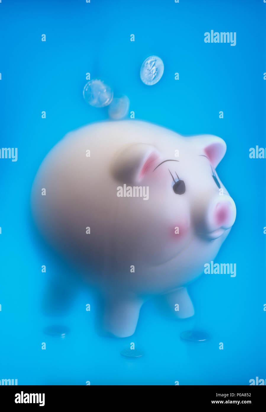 Conceptual image of coins falling from the sky into a piggy bank with a soft ethereal background - Stock Image