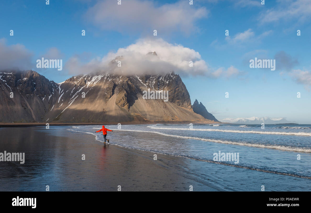 Man runs in a good mood on a black sandy beach, mountains Klifatindur, Eystrahorn and Kambhorn, headland Stokksnes - Stock Image