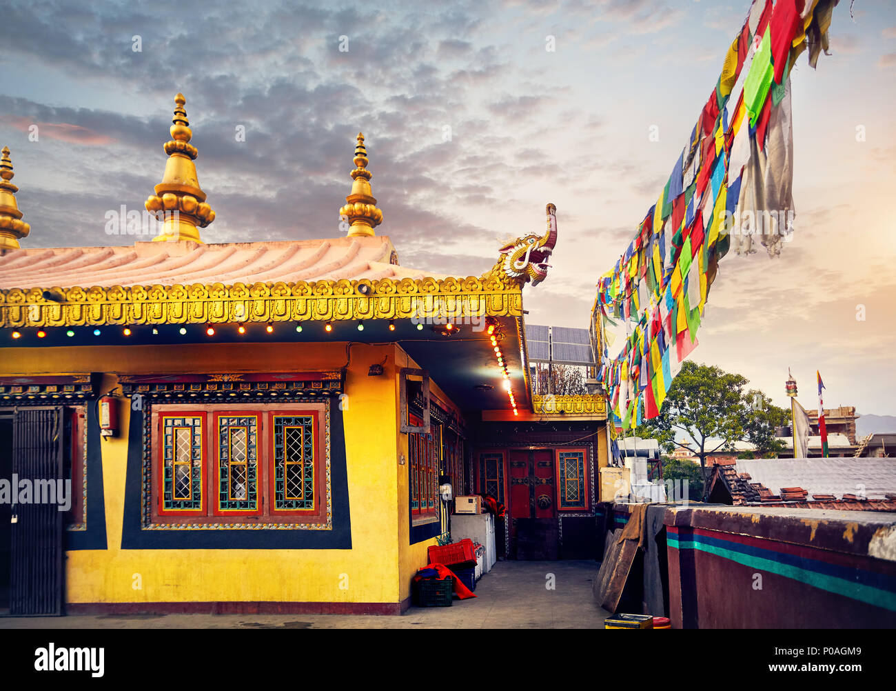Buddhist monastery roof at Bodnath Great Buddhist complex with golden dragon and prayer flags in Kathmandu - Stock Image