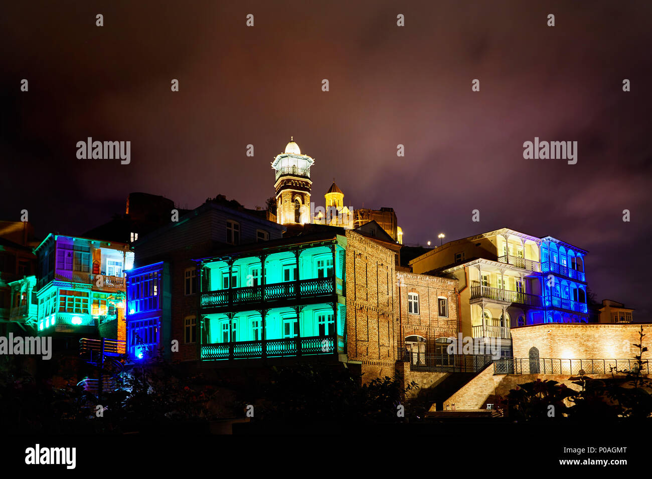 Narikala fortress and Public Sulfuric bath with colorful lighting at night in central Tbilisi, Georgia - Stock Image