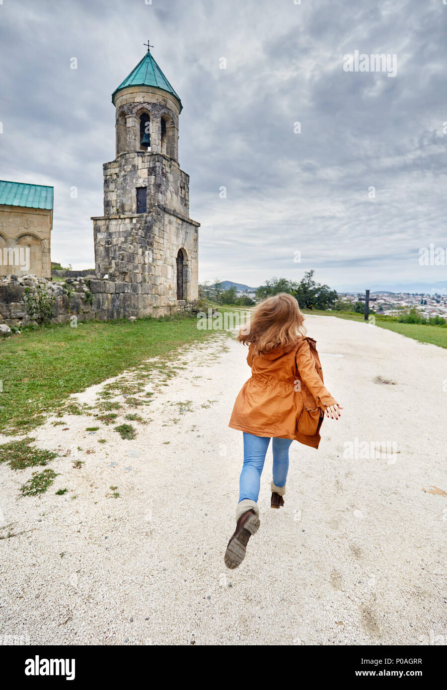 Woman running to the Chapel tower of Bagrati church at overcast sky in Kutaisi, Georgia - Stock Image