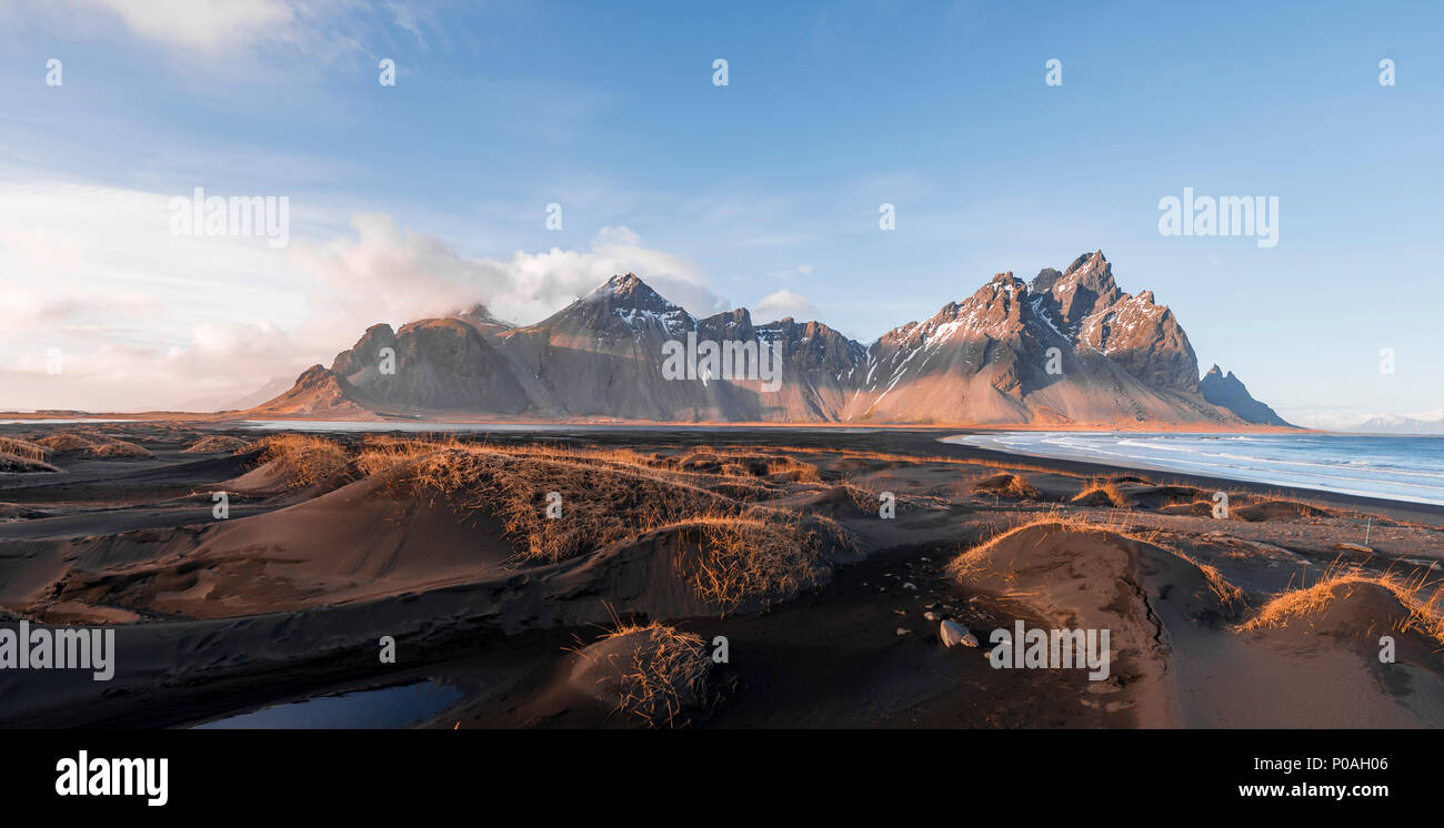 Evening atmosphere at the long lava beach, black sandy beach, dunes covered with dry grass, mountains Klifatindur Stock Photo