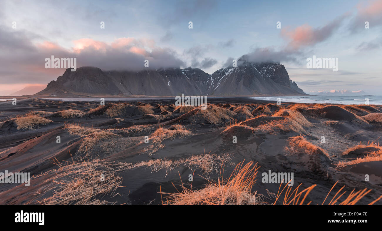 Evening atmosphere at the lava beach, black sandy beach with dunes, overgrown with dry grass, mountains Klifatindur Stock Photo