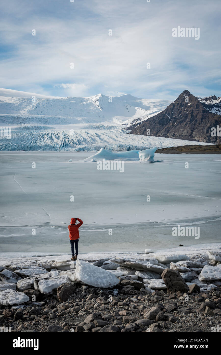 Man stands at frozen lagoon with ice floe, mountains, Fjallsárlón Glacier Lagoon, South Iceland, Iceland Stock Photo