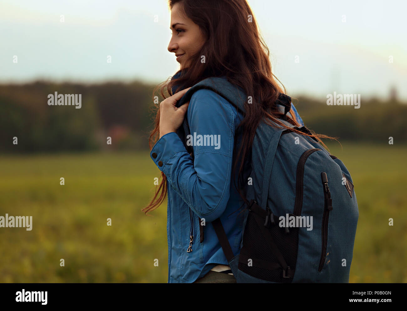 Happy backpacking adventurous woman have a camping trip with blue huge haversack on nature summer evening background. closeup portrait - Stock Image