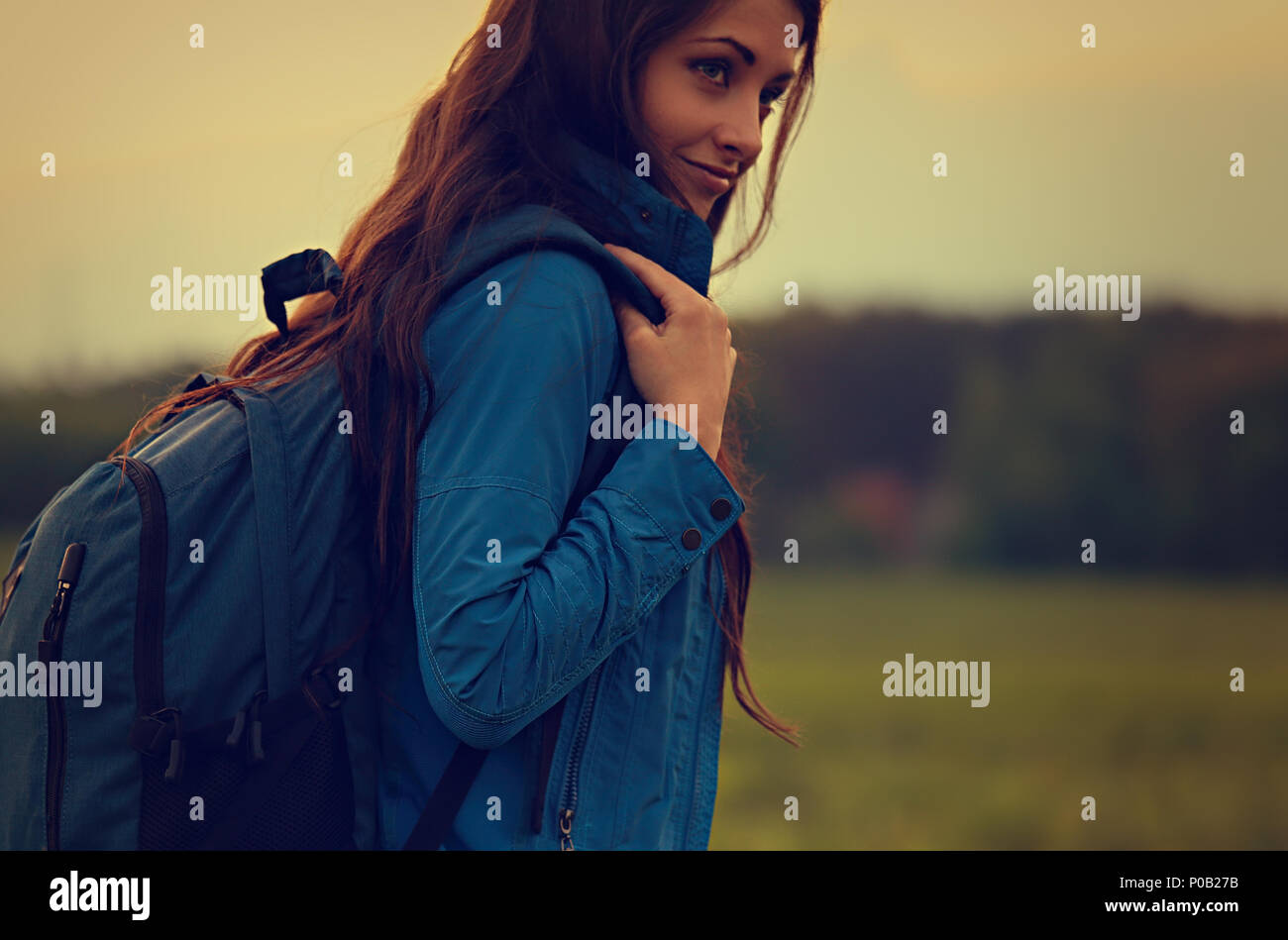 Happy backpacking adventurous woman have the camping trip with blue huge haversack on nature summer background. Toned closeup portrait - Stock Image