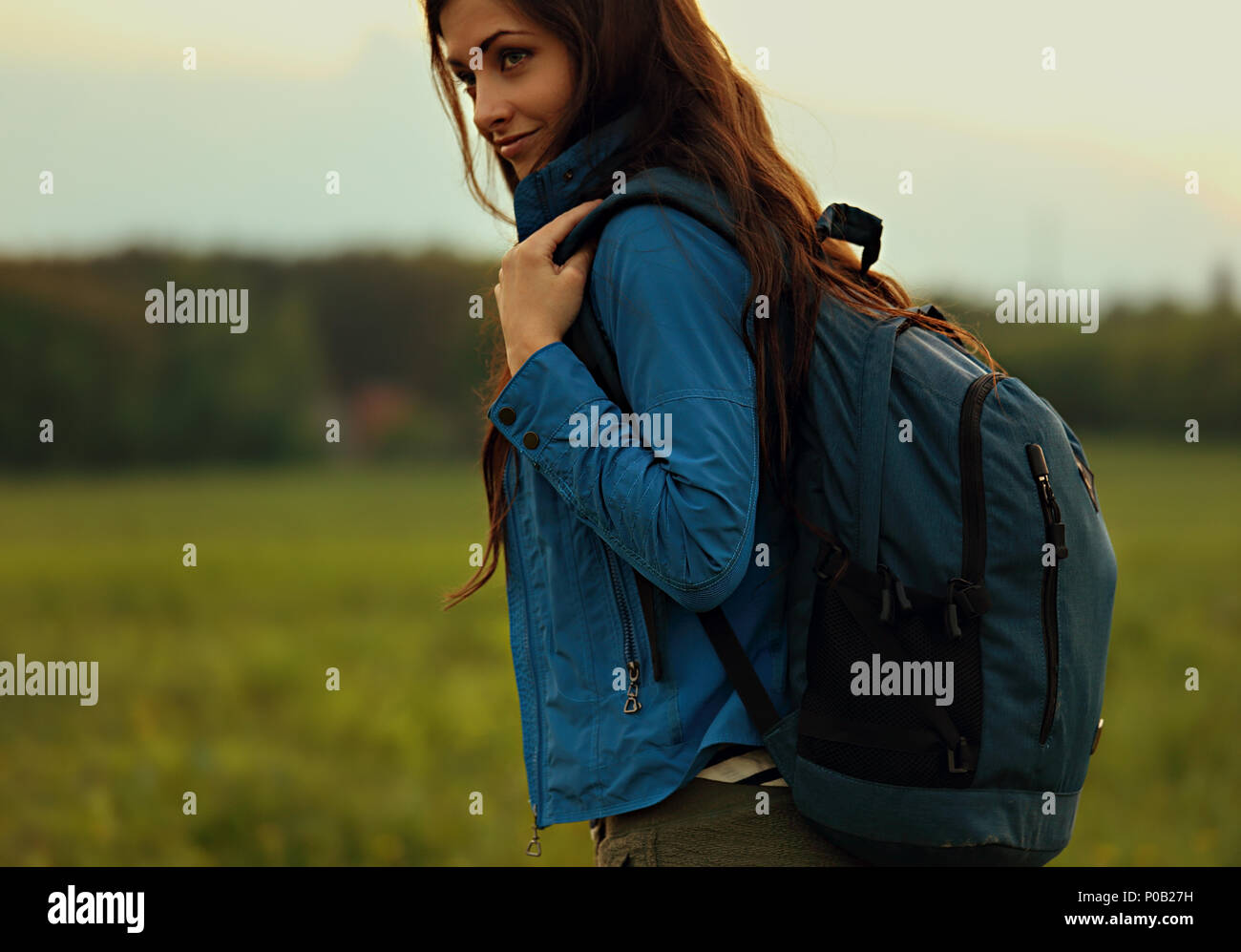 Happy backpacking adventurous woman have a trip with blue huge haversack on nature summer background - Stock Image