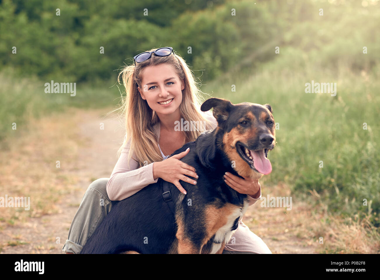 Happy smiling black dog wearing a walking harness sitting facing its pretty young woman owner who is caressing it with a loving smile outdoors in coun - Stock Image