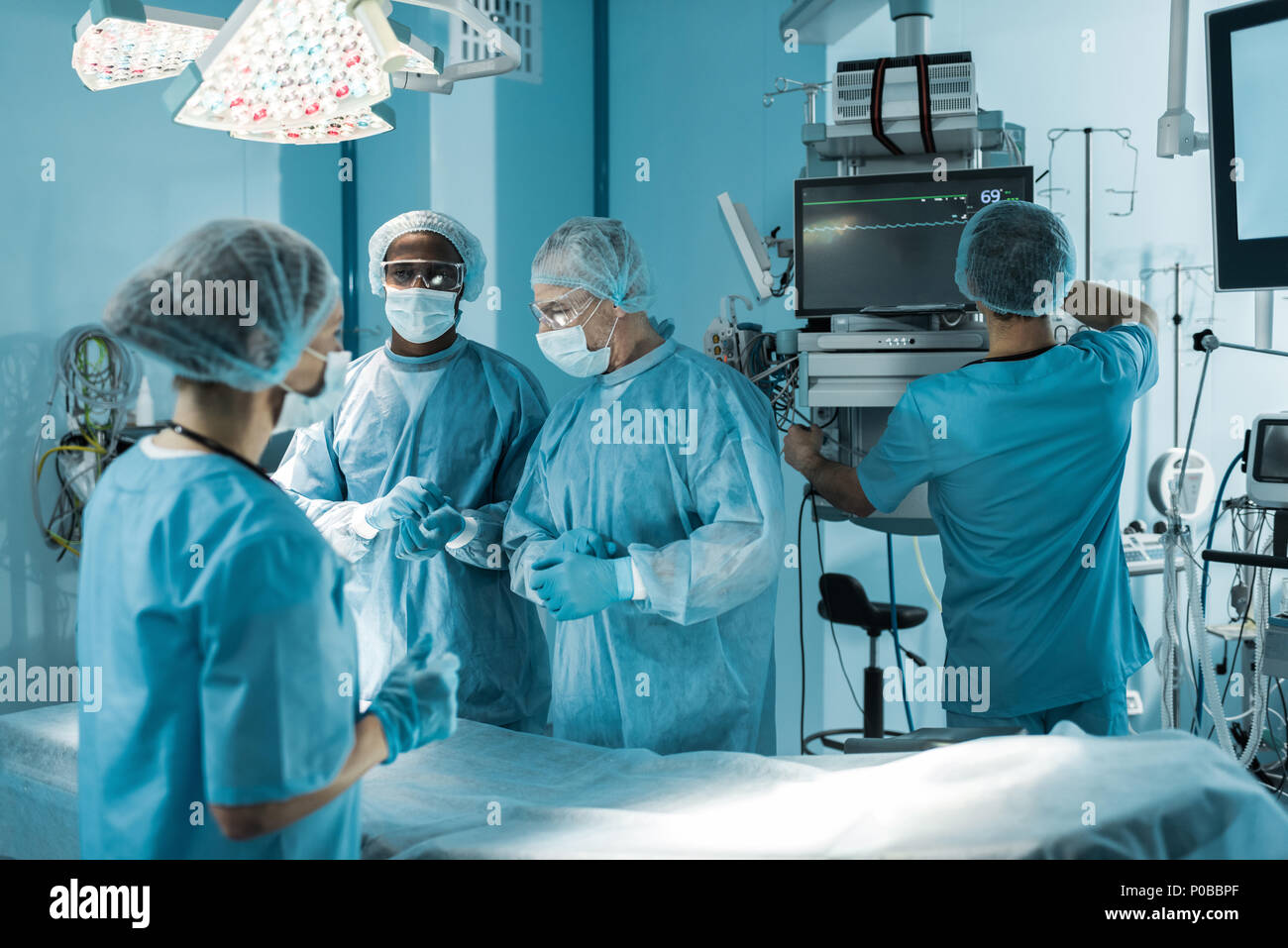 four multicultural doctors preparing for surgery - Stock Image