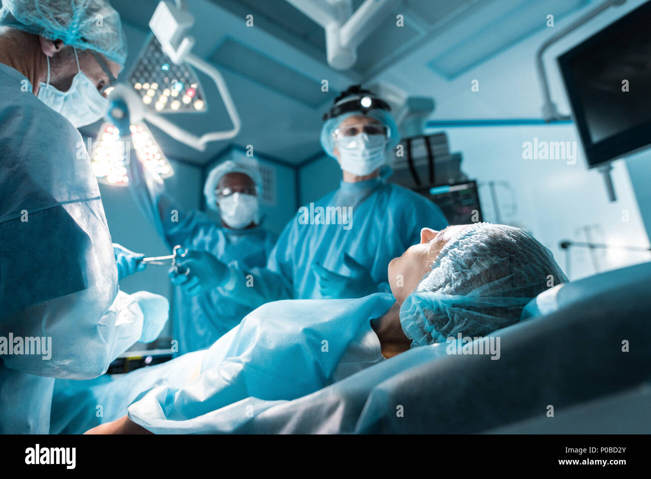 patient lying on operating table in surgery room - Stock Image