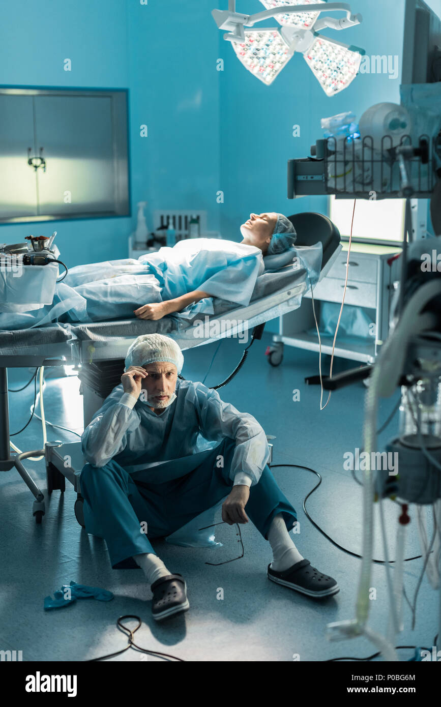 doctor sitting on floor near patient on operating table - Stock Image