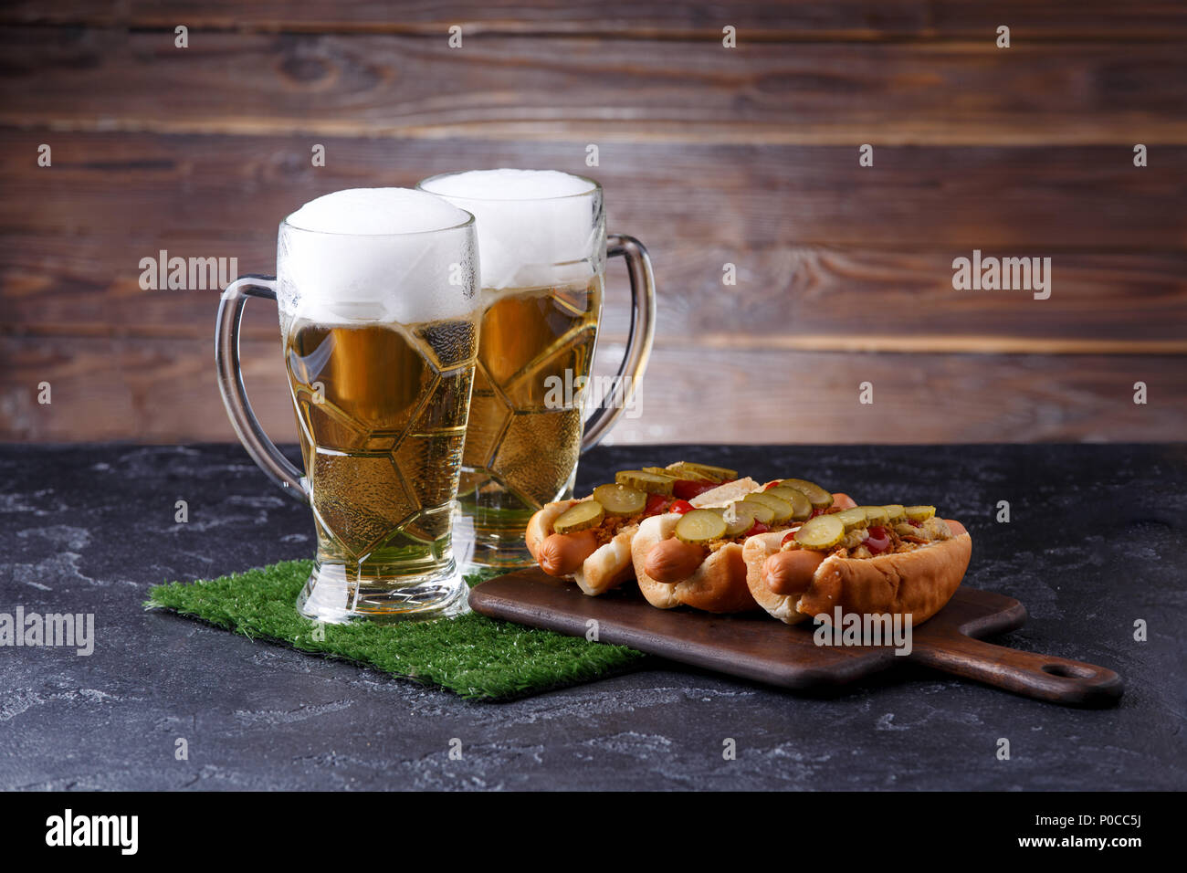 Photo of two mugs of foam beer, green grass with football, hotdogs Stock Photo