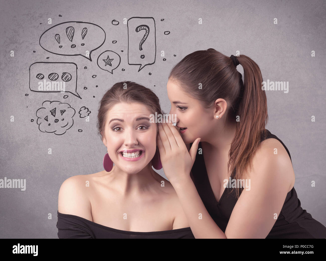 Two girls chatting and sharing their secrets concept with drawn chat bubbles on the background urban wall. - Stock Image