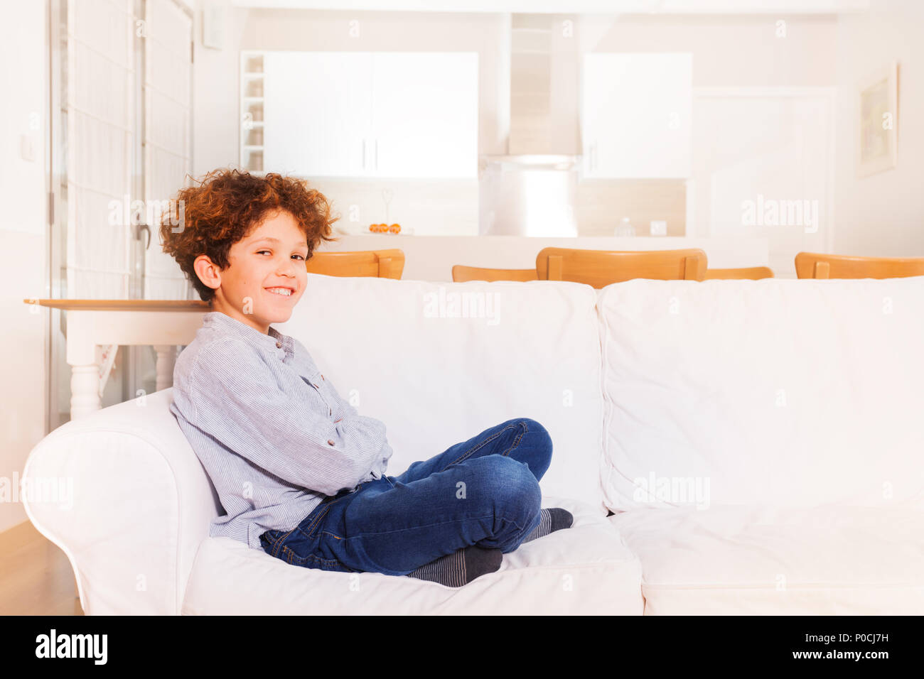 Happy preteen boy sitting on white comfortable sofa in the living room - Stock Image