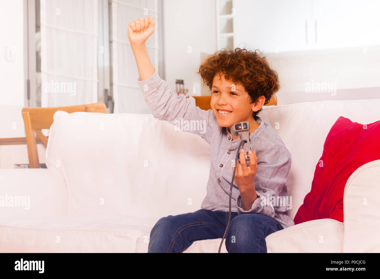 Portrait of happy preteen boy celebrating victory, playing video games at home - Stock Image